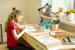 Wenig schöne Mädchenmalerei mit den Aquarellen, zu Hause sitzend am Tisch Kinderkreativität, Erholung, Entwicklung lizenzfreies stockbild