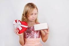 Wenig schönes blondes Mädchen, das schönes Geschenk für den Valentinsgrußtag, Geburtstag, neues Jahr hält lizenzfreie stockfotos