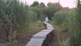 Wenig schönes Mädchen in den weißen Kleiderläufen entlang Holzbrücke unter grünem hohem Gras stock footage