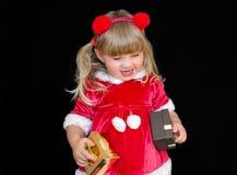 Wenig schönes Mädchen in einer Weihnachts-Sankt-Klage, mit Pelzbällen auf ihrem Kopf, hält Geschenke in ihren Händen und freut si stockbild
