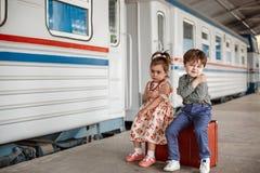 Wenig schönes Mädchen im Retro- Kleid nimmt an der Station mit einem kleinen Jungen in der Weinlesekleidung mit Retro- Koffer Abs lizenzfreie stockfotografie