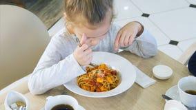 Wenig schmutziges Mädchenessen unvorsichtig ihre Teigwaren im Café stockbild