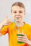 Wenig schnitt den Jungen, der eine frische grüne Limonade durch Stroh trinkt Stockfotografie