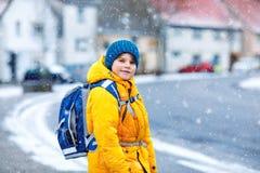 Wenig Schulkinderjunge der grundlegenden Klasse gehend zur Schule während der Schneefälle Glückliches Kind, das Spaß hat und mit  stockfotografie