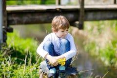 Wenig Schulkinderjunge, der nahe Fluss mit Blumen in den Händen sitzt Lizenzfreie Stockbilder