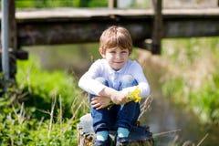 Wenig Schulkinderjunge, der nahe Fluss mit Blumen in den Händen sitzt Lizenzfreie Stockfotos