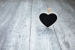 Wenig schwarzes Herz auf einem hölzernen grauen Hintergrund Stockbild