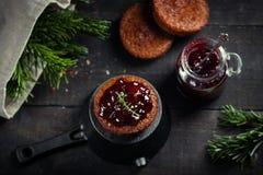 Wenig selbst gemachtes Muffin der Schokolade geschmückt mit Kirschmarmelade Dunkle schwermütige Art Draufsicht, selektiver Fokus stockfotografie