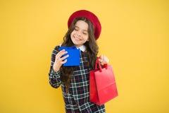 Wenig shopaholic Kindermode glückliches Mädchen im französischen Barett Kind mit Geschenkbox auf gelbem Hintergrund kleines Mädch stockfoto