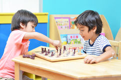 Wenig siblimg Junge, der Schach spielt Lizenzfreies Stockfoto