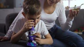 Wenig Sohn, der Botanik unter Mikroskop studiert stock footage