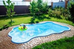 Wenig Spaßmädchen ist Swimmingpool Lizenzfreie Stockfotos