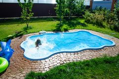 Wenig Spaßmädchen ist Swimmingpool Lizenzfreies Stockfoto