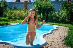 Wenig Spaßmädchen ist Swimmingpool Lizenzfreie Stockfotografie