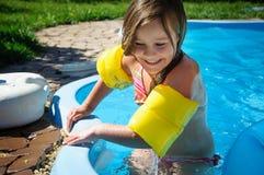 Wenig Spaßmädchen ist Swimmingpool und Lächeln Lizenzfreie Stockbilder