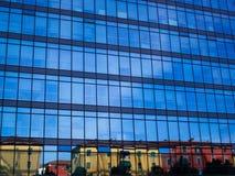 Wenig Stadt färbte die Häuser, die über ein großes widergespiegeltes Unternehmensgebäude mit blauem Himmel als Hintergrund nachde Lizenzfreie Stockfotos
