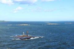 Wenig Steininsel in einem Meer des blauen Himmels mit weißen Wolken lizenzfreies stockfoto