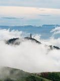 Wenig Tempel auf nebeligem Berg Stockbild