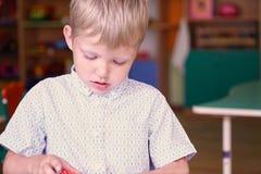 Wenig trauriger und frustrierter Junge, der mit bunten Plastikziegelsteinen am Tisch im Kindergarten spielt lizenzfreies stockbild
