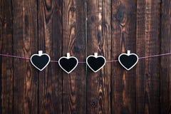 Wenig vier Herzen auf einem Seil hängen an einem rosa Seil auf einem hölzernen Hintergrund Stockfotografie