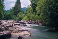 Wenig Wasserfall in funkelndem Fluss Stockbild