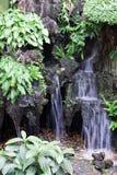 wenig Wasserfall unter Grünpflanzen Stockfotos