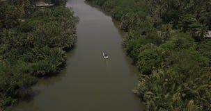 Wenig weißes Safariboot, das weit weg von der Brummenkamera entlang ruhigem ruhigem Dschungelfluß mitten in Wildnis segelt stock footage