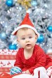Wenig Weihnachtsbaby in Sankt-Kostüm Kind, das blauen Ball nahe Lichterkettehintergrund hält Lizenzfreie Stockfotografie