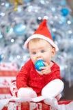 Wenig Weihnachtsbaby in Sankt-Kostüm Kind, das blauen Ball nahe Lichterkettehintergrund hält Stockbilder