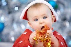Wenig Weihnachtsbaby in Sankt-Kostüm Kind, das blauen Ball nahe Lichterkettehintergrund hält Stockfotografie