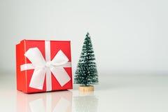 Wenig Weihnachtsbaum mit verziertem Weihnachtsgeschenk im roten Kasten und im weißen Band Feiertagskonzept des neuen Jahres mit l Lizenzfreies Stockfoto