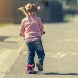 Wenig zwei Jahre alte Mädchen, die ihren Roller reiten Lizenzfreies Stockbild