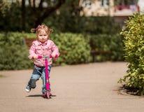 Wenig zwei Jahre alte Mädchen, die ihren Roller reiten Lizenzfreie Stockbilder