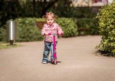 Wenig zwei Jahre alte Mädchen, die ihren Roller reiten Stockbilder