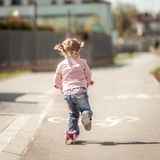Wenig zwei Jahre alte Mädchen, die ihren Roller reiten Lizenzfreie Stockfotografie