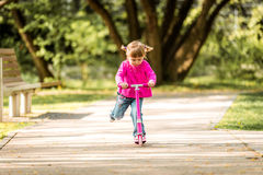 Wenig zwei Jahre alte Mädchen, die ihren Roller reiten Lizenzfreie Stockfotos