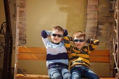Wenig zwei Jungen in der Sonnenbrille, die auf ein Schwingen fährt Portrait von zwei nassen Pelikanen auf dunklem Hintergrund Stockfotografie