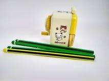 Wenige Bleistifte und mechanischer Bleistiftspitzer auf Weiß stockfoto