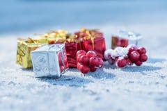 Wenige Geschenke und rote Beeren auf eisiger Oberfläche mit hellblauem bokeh Hintergrund Stockfoto