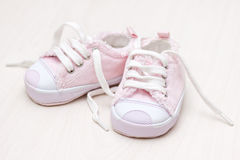 Wenige girlie Babyschuhe auf einem hölzernen Fußboden Stockfoto