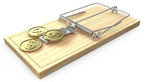 Wenige goldene Münzen auf einer Mäusefalle Stockbild