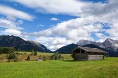 Wenige Hütten auf greem Wiesen über blauem Himmel Lizenzfreie Stockfotos