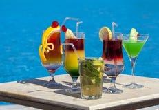Wenige mehrfarbige Cocktails durch das Pool stockbilder