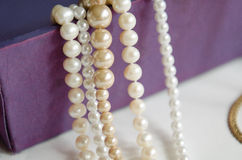 wenige Perlen von den Perlen, die an einem purpurroten Geschenkboxhalskettenschmuck hängen Stockbild