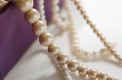 wenige Perlen von den Perlen, die an einer purpurroten Geschenkbox hängen Lizenzfreies Stockbild