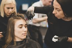 Wenkbrauw het verven De meester schildert wenkbrauwen met henna aan een mooi meisje, schildert met een borstel in de salon van ee royalty-vrije stock fotografie