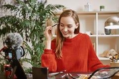 Wenkbrauwen modellering Glimlachende en jonge blogger die rode sweater dragen die haar wenkbrauwen modelleren terwijl het registr stock foto's