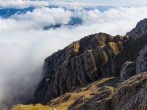 Wenn Sie an die Spitze des Berges und der Wolken gelangen, seien Sie an Ihren Füßen Stockbild