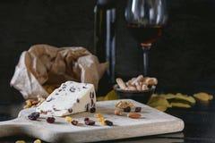 Wensleydale-Käse mit Moosbeeren, Rotwein, Honig, Nüsse, Rosinen auf hölzernem Schneidebrett lizenzfreie stockbilder