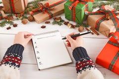 Wenslijst voor Kerstmis Vrouwenhanden met notitieboekje en pen Spartak, klokken, kaneel, noten Het concept van het nieuwjaar Stock Foto's
